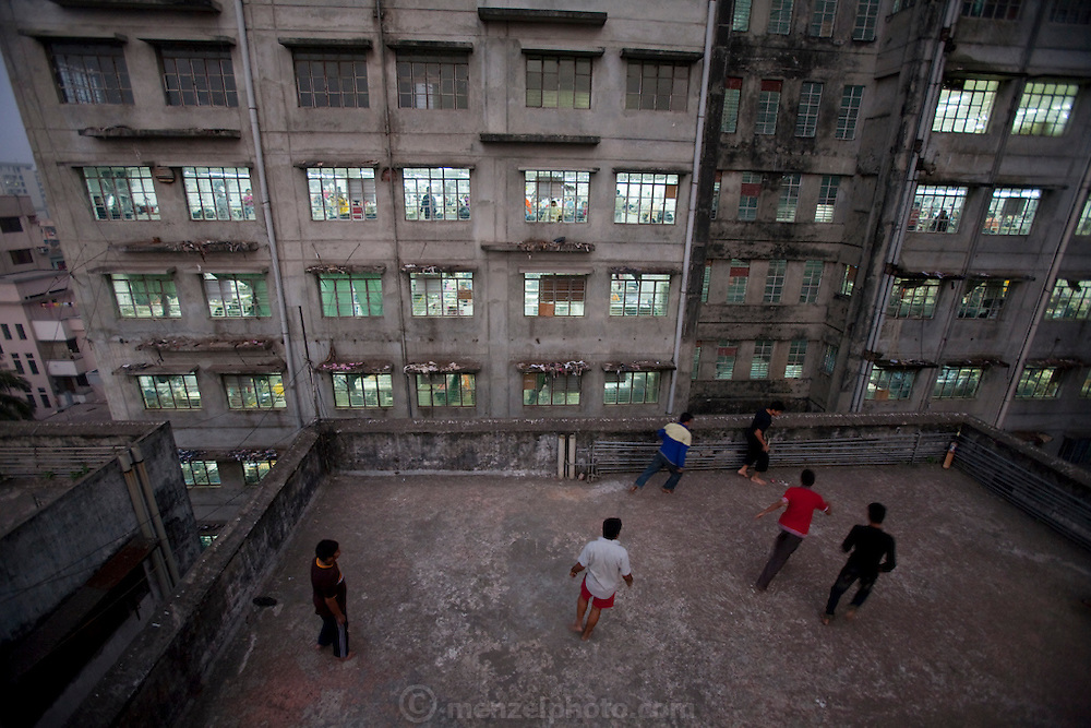 Young men play cricket and soccer on the roof of a building next to the Ananta Clothing Factory on Elephant Road in Dhaka, Bangladesh.