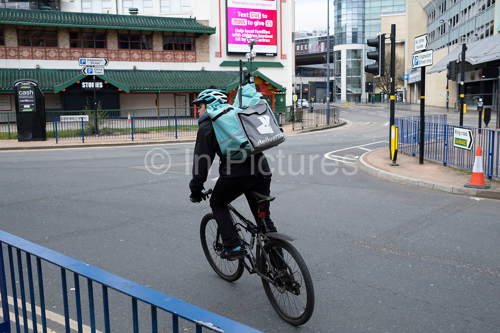 Deliveroo delivery rider in Birmingham city centre, which is virtually deserted due to the Coronavirus outbreak on 31st March 2020 in Birmingham, England, United Kingdom. Following government advice most people are staying at home leaving the streets quiet, empty and eerie. Coronavirus or Covid-19 is a new respiratory illness that has not previously been seen in humans. While much or Europe has been placed into lockdown, the UK government has announced more stringent rules as part of their long term strategy, and in particular social distancing.
