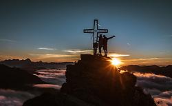 THEMENBILD - Wanderer mit dem Gipfelkreuz des Tristkogel während des Sonnenaufgangs über den Wolken, aufgenommen am 16. September 2018 in Saalbach Hinterglemm, Österreich // Hiker with the summit cross of the Tristkogel during the sunrise over the clouds, Saalbach Hinterglemm, Austria on 2018/09/16. EXPA Pictures © 2018, PhotoCredit: EXPA/ Stefanie Oberhauser