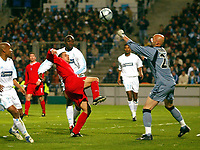 Photo: Scott Heavey.<br /> Olympique de Marseeille v Liverpool. UEFA Cup 4th Round, second leg.<br /> Fabian Barthez (R) punches clear from Michael Owen