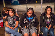 """13 JULY 2012 - FT DEFIANCE, AZ:  TANIA LEMMON (left) prays with Navajo teenagers during the youth service at the 23rd annual Navajo Nation Camp Meeting in Ft. Defiance, north of Window Rock, AZ, on the Navajo reservation. Preachers from across the Navajo Nation, and the western US, come to Navajo Nation Camp Meeting to preach an evangelical form of Christianity. Evangelical Christians make up a growing part of the reservation - there are now more than a hundred camp meetings and tent revivals on the reservation every year. The camp meeting in Ft. Defiance draws nearly 200 people each night of its six day run. Many of the attendees convert to evangelical Christianity from traditional Navajo beliefs, Catholicism or Mormonism. """"Camp meetings"""" are a form of Protestant Christian religious services originating in Britain and once common in rural parts of the United States. People would travel a great distance to a particular site to camp out, listen to itinerant preachers, and pray. This suited the rural life, before cars and highways were common, because rural areas often lacked traditional churches.  PHOTO BY JACK KURTZ"""