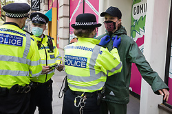An activist from Palestine Action is searched by a Metropolitan Police officer during a protest outside the UK headquarters of Elbit Systems, an Israel-based company developing technologies used for military applications including drones, precision guidance, surveillance and intruder-detection systems, on 11th May 2021 in London, United Kingdom. The activists were protesting against the company's presence in the UK and in solidarity with the Palestinian people following attempts at forced evictions of Palestinian families in the Sheikh Jarrah neighbourhood of East Jerusalem, the deployment of Israeli forces against worshippers at the Al-Aqsa mosque during Ramadan and air strikes on Gaza which have killed several children.