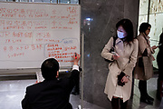 A woman holds her cellphone as she checks a whiteboard in the basement of the Cerulean Tower hotel in Shibuya for information on transport options  after a magnitude .9 earthquake hit the Tohoku region of north east Japan causing tremors in Tokyo that stopped the train and cellphone networks. Many people were stranded in the centre of Tokyo over night. Tokyo, Japan Friday March 11th 2011