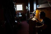 Rafal Flieger works on his laptop in his dark dorm room at the Polish Polar Station, Hornsund, Svalbard.