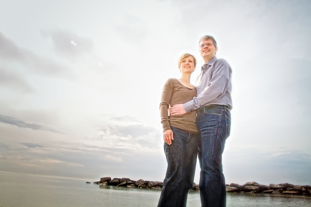 A married couple hug and look off into the distance at the Toronto waterfront.