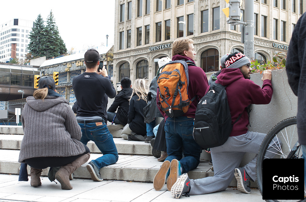 People take cover while heavily armed police enter the Rideau Centre which was placed under lock down following the shooting of Cpl. Nathan Cirillo. October 22, 2014.