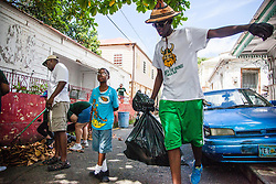 Irvin Mason hauls a bag of trash collected by volunteers.  Residents and volunteers gather for the Garden Street neighborhood cleanup and block Party hosted by E's Garden and Things, Long Path/Garden Street Community Association, and the Economic Development Authority's Enterprise and Commerical Zone Commission.  St. Thomas, USVI.  5 September 2015.  © Aisha-Zakiya Boyd