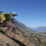 Lloyd Jenks from Wellington in action during the NZBNZ South Island Downhill Cup mountain bike downhill series held on The Remarkables face with a stunning backdrop of the Wakatipu Basin. 150 riders took part in the two day event.  Queenstown, Otago, New Zealand. 9th January 2012. Photo Tim Clayton
