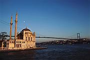 Bosphorus River, Istanbul, Turkey. The Ottoman mosque called Mecidiye Camii sits at the foot of the Bogazici bridge. Islam, Muslim, Architecture, Religion.