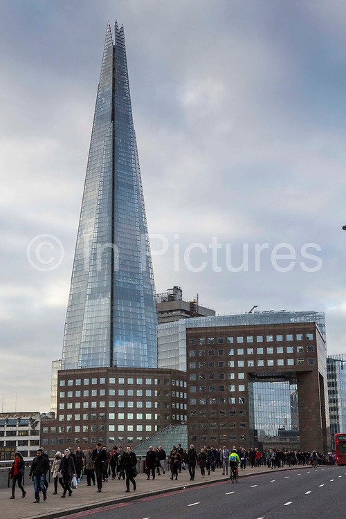 Commuters cross London bridge with the Shard in the background to get to work in the city of London.