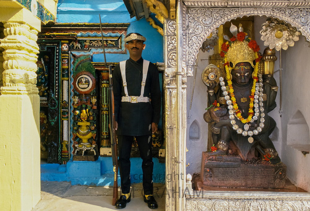 Ceremonial guard and garlanded religious statue, Kathmandu, Nepal