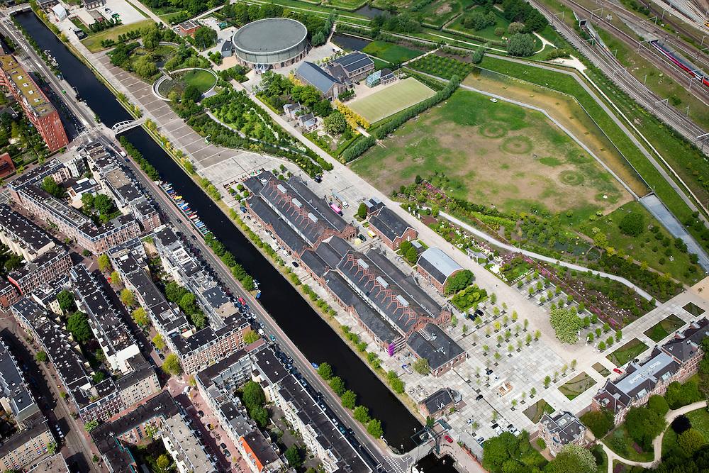 Nederland, Amsterdam, Westerpark, 25-05-2010. Overzicht Cultuurpark Westergasfabriek. Linksonder Staatsliedenbuurt, aan het water de gebouwen van de voormalige fabriek (Zuiveringshal, daarachter Ketelhuis en Machingebouw). Midden het park (architecte Kathryn Gustafson) met de voormalige gashouder. Rechtsonder het stadsdeelkantoor..Het ernstige vervuilde terrein is gesaneerd de voormalige fabrieksgebouwen hebben een culturele bestemming gekregen, het terrein wordt gebruikt voor manifestaties, tentoonstelling, expositie, cultuur, industrieel en cultureel erfgoed: cultuurpark. .Overview Culture Park Westergasfabriek..Left of the canal to Haarlem Staatsliedenbuurt, adjacent to the water the buidling of the former plant. In the middle the park with the former gasometer..The former industrial buildings have a cultural destination, the site is used for events, exhibitions, cultural manifestations: culture park..luchtfoto (toeslag), aerial photo (additional fee required).foto/photo Siebe Swart