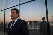 Dr Mustafa Palancioglu stands outside the Ommer Hotel, where the ruling AKP held it's business forum in Kayseri, Turkey. Reflected is a newly built bus terminal serving rural and national destinations.