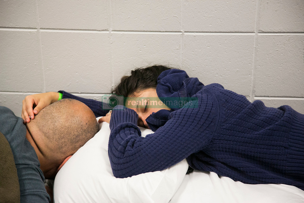 September 10, 2017 - St. Petersburg, Florida, U.S. - YAYA LOPEZ holds her fiance HOWARD LOPEZ's head while they sleep in a hallway at John Hopkins Middle School. The school filled classrooms and hallways with people evacuating before Hurricane Irma makes landfall. The shelter welcomes people from the area with pets and those with special needs. (Credit Image: © Eve Edelheit/Tampa Bay Times via ZUMA Wire)