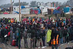 """Dschungel von Calais: Das wilde Fl¸chtlingslager wird ger‰umt und die Fl¸chtlinge in Aufnahmezentren verteilt / 241016 ***Calais, Pas-de-Calais, France - 24.10.2016    <br />  <br /> Refugees line up to leave the camp. Start of the eviction on the so called îJungle"""" refugee camp on the outskirts of the French city of Calais. Refugees and migrants leaving the camp to get with buses to asylum facilities in the entire country. Many thousands of migrants and refugees are waiting in some cases for years in the port city in the hope of being able to cross the English Channel to Britain. French authorities announced a week ago that they will evict the camp where currently up to up to 10,000 people live.<br /> <br /> <br /> Fluechtlinge stehen in einer Reihe um das Camp zu verlassen. Beginn der Raeumung des so genannte îJungleî-Fluechtlingscamp in der franzˆsischen Hafenstadt Calais. Fluechtlinge und Migranten verlassen das Camp um mit Bussen zu unterschiedlichen Asyleinrichtungen gebracht zu werden. Viele tausend Migranten und Fluechtlinge harren teilweise seit Jahren in der Hafenstadt aus in der Hoffnung den Aermelkanal nach Groflbritannien ueberqueren zu koennen. Die franzoesischen Behoerden kuendigten vor einigen Wochen an, dass sie das Camp, indem derzeit bis zu bis zu 10.000 Menschen leben raeumen werden. <br /> <br /> Photo: Bjoern Kietzmann"""
