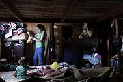 """Noelia (19) acomoda la ropita de su bebé Samir (6 meses) en la habitación de su casa mientras su hijita mayor Abril (3) juega con su hermanito a quien le dieron el alta médica luego de una semana de internación en el Hospital Público de la Ciudad Capital de la Rioja donde se le realizó su primera cirugía reparadora por fisura naso labio alveolo palatina unilateral (labio leporino). La región del noroeste Argentino, presenta una tasa alarmante de nacimientos de niños con labio leporino. Son malformaciones congénitas que requieren de tratamientos multidisciplinarios y de varias cirugías reparadoras de labio, nariz, encías y paladar. La falta de acceso a los tratamientos y/o cirugías reparadoras, puede originar cuadros graves de desnutrición infantil, deformaciones cráneo faciales y severas problemáticas en la expresión oral del lenguaje. Entre otras discapacidades adquiridas. """"Cuando nació Samir (6 meses) lloré por tres días seguidos. No entendía la razón por la que tenía todo su paladar abierto, pensé que nunca lo iba a poder alimentar"""" -Dice Noelia- Ella vive a 4 horas de distancia con el Hospital de la Ciudad Capital en el que se realizan las cirugías. Al igual que las otras madres, también ejerce su rol de """"cuidadora"""" y se encuentra en una situación muy compleja a nivel económico. """"Por ahora, sólo pienso en la primera cirugía de mi bebé- Dice. -Más adelante veré cómo le hago. Necesito disponer de mucho dinero extra para los pasajes"""