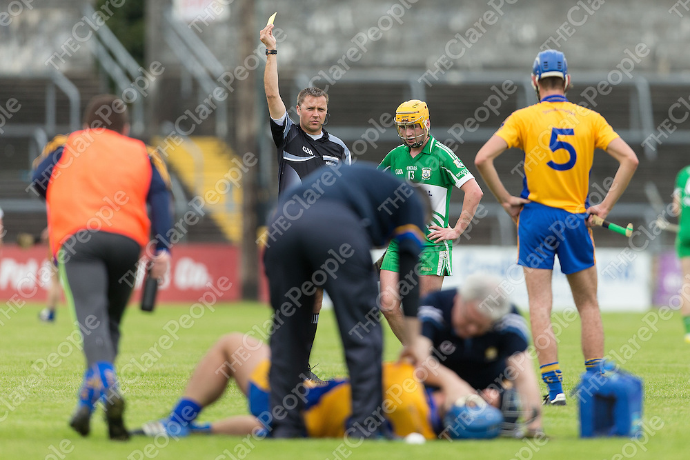 Wolfe Tones Sean Costelloe receives a yellow card while Sixemilebridge's Caimin Morey receives treatment