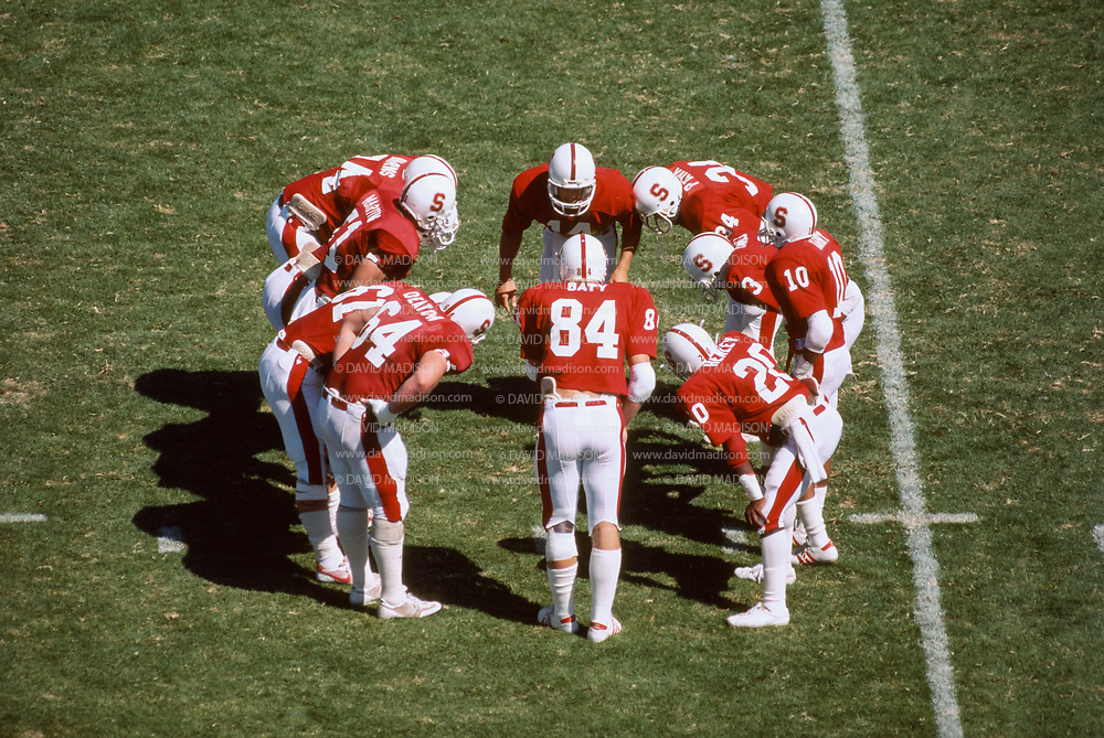 COLLEGE FOOTBALL:  The Stanford Cardinal offense huddles during a game in the 1984 season played at Stanford Stadium in Palo Alto, California.  Visible players include quarterback John Paye #14, Greg Baty #84, Thomas Henley #20, Emile Harry #10, Jeff James #3, Jeff Deaton #64.  Photograph by David Madison | www.davidmadison.com