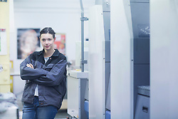 Portrait of a print worker standing with her arms crossed, Freiburg im Breisgau, Baden-Wuerttemberg, Germany