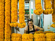 10 SEPTEMBER 2013 - BANGKOK, THAILAND: A woman prepares marigold arrangements for sale in the Bangkok flower market. The Bangkok Flower Market (Pak Klong Talad) is the biggest wholesale and retail fresh flower market in Bangkok. The market is busiest between 3:30AM and 6AM. Thais grow and use a lot of flowers. Some, like marigolds and lotus, are used for religious purposes. Others are purely ornamental.    PHOTO BY JACK KURTZ