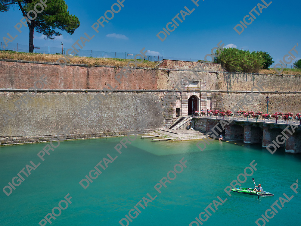 A person rests under the bridge at the entrance to the village of Peschiera del Garda, Italy while another person sails in a kayak during a summer afternoon