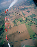 Banking hard right over the agricultural Lincolnshire countryside are the elite 'Red Arrows', Britain's prestigious Royal Air Force aerobatic team, who have commenced an In-Season Practice (ISP) training flight near their base at RAF Scampton. They turn at a ninety degree angle, two trailing white organic smoke before reforming in front of a local crowd at the airfield and working through a 25-minute series of display manoeuvres that are loved by thousands at summer air shows. Their objective is to appear perfectly spaced from a ground perspective. Freshly-ploughed English fields with properties, roads and hedgerows are seen below. After some time off, spare days like this are used to hone their manual aerobatic and piloting skills before re-joining the air show circuit. Since 1965 they've flown over 4,000 shows in 52 countries.   .