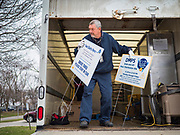 "26 MARCH 2020 - DES MOINES, IOWA: A worker unloads signs before hot lunch distribution at Weeks Middle School. Des Moines Public Schools (DMPS) started distributing hot lunches Thursday, the first day students were supposed to return to school. Schools will now remain closed until 13 April. Meals were distributed with ""social distancing"" in mind. On Thursday morning, 24 March, Iowa reported 175 confirmed cases of the Coronavirus (SARS-CoV-2) and COVID-19. Restaurants, bars, movie theaters, places that draw crowds are closed until 07 April. The Governor has not ordered ""shelter in place""  but several Mayors, including the Mayor of Des Moines, have asked residents to stay in their homes for all but the essential needs. People are being encouraged to practice ""social distancing"" and many businesses are requiring or encouraging employees to telecommute.         PHOTO BY JACK KURTZ"