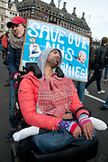 Tens of thousands of health workers, activists and members of the public protested against austerity and cuts in the NHS National Health Service on March 4th 2017 in London, United Kingdom. A young man with severe disabilities sits in his wheelchair in front of Parliament with a home-made placard saying Save our NHS.