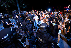 Charlotte-Mecklenburg police officers in riot gear form a line as protestors fill an area of Old Concord Rd. on Tuesday night, Sept. 20, 2016 in Charlotte, N.C. The protest began on Old Concord Road at Bonnie Lane, where a Charlotte-Mecklenburg police officer fatally shot a man in the parking lot of The Village at College Downs apartment complex Tuesday afternoon. The man who died was identified late Tuesday as Keith Scott, 43, and the officer who fired the fatal shot was CMPD Officer Brentley Vinson. Photo by Jeff Siner/Charlotte Observer/TNS/ABACAPRESS.COM