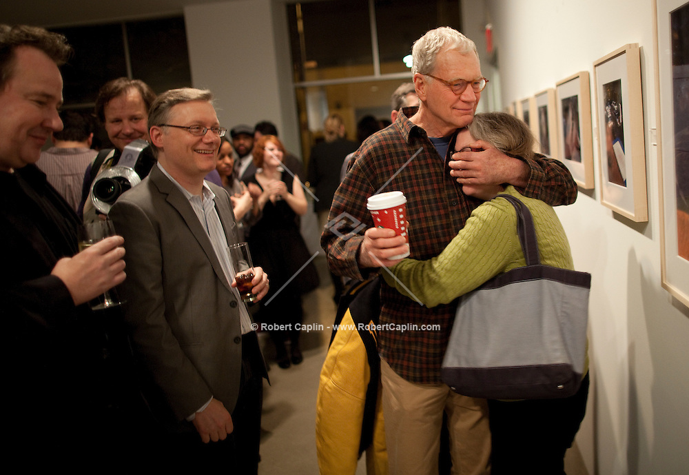 """David Letterman embraces his producer, Barbara Gaines, at his staff's holiday party and photo gallery exhibition by his staff writer Steve Young, left, entitled """"CELEBRIGUM"""" held at Ameringer McEnery Yohe Gallery  in New York. ..Photo by Robert Caplin."""