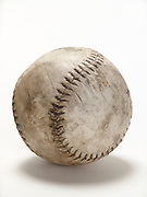 Still life of baseball on white surface.