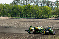 A large agricultural tractor pulls a planter implement to seed the field