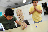 """Tony Castro, left, is cool and calm while Jovanny Melo's body language says it all during their after-school game of Jenga at the Hebbron Family Center on Monday. The boys are both 10, and in the fifth-grade at Loma Vista Elementary School in Salinas.  <br /> <br /> Jenga is a game of patience and dexterity, quite popular since its introduction to the USA in the mid-1980s. The name Jenga is from Swahili, meaning """"to build."""" The trick, of course, is not only to remove a tile from the original tower of 54, but to replace it at the top, creating an increasingly unstable structure until… <br /> <br /> Kids visiting the Hebbron Family Center can get help with their homework from staff, play games, use the computers, take karate classes, and join a variety of other enrichment activities throughout the year. <br /> <br /> The City of Salinas Recreation-Park Division offers free after school programs for youth at several of its recreation facilities Monday - Friday between the hours of 3:00 p.m. - 5:30 p.m. These programs offer a safe, fun and positive environment for youth. For more information, please visit http://www.ci.salinas.ca.us/services/recreation/kids_programs.cfm"""