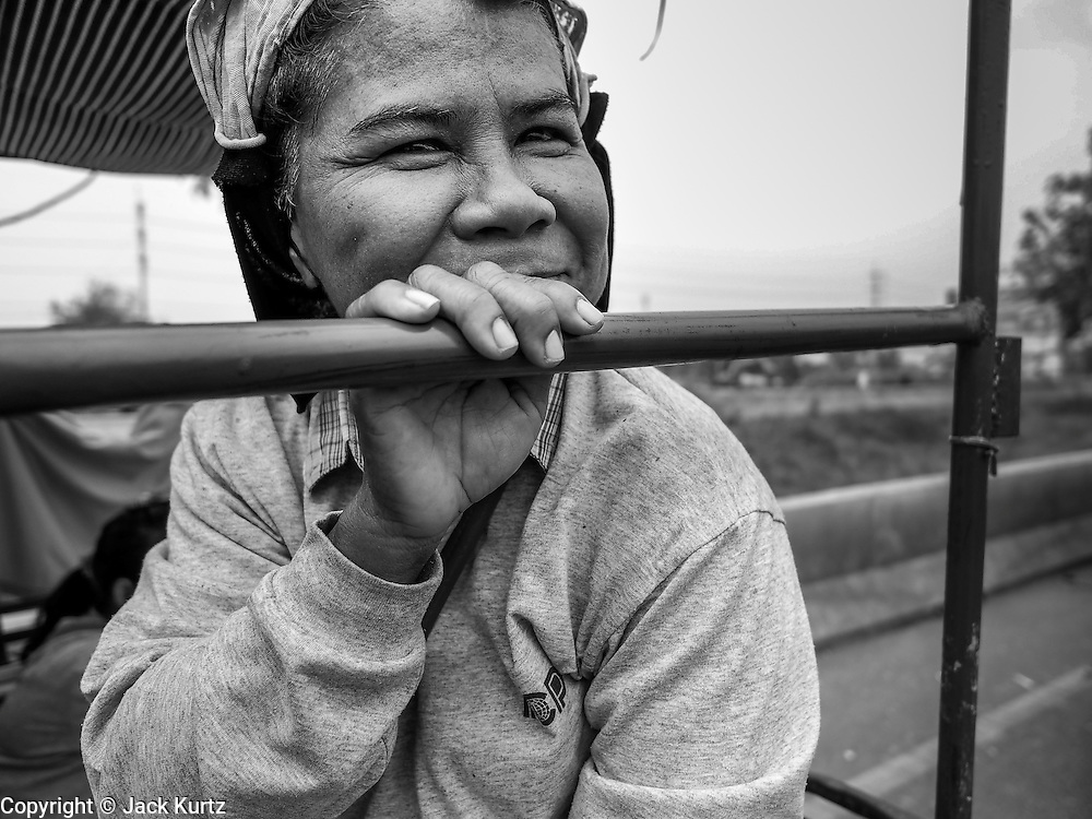 21 FEBRUARY 2014 - KHLONG CHIK, PHRA NAKHON SI AYUTTHAYA, THAILAND: A Thai farmer's wife on the highway south of Ayutthaya. About 10,000 Thai rice farmers, traveling in nearly 1,000 tractors and farm vehicles, blocked Highway 32 near Bang Pa In in Phra Nakhon Si Ayutthaya province. The farmers were traveling to the airport in Bangkok to protest against the government because they haven't been paid for rice the government bought from them last year. The farmers turned around and went home after they met with government officials who promised to pay the farmers next week. This is the latest blow to the government of Yingluck Shinawatra which is confronting protests led by anti-government groups, legal challenges from the anti-corruption commission and expanding protests from farmers who haven't been paid for rice the government bought.    PHOTO BY JACK KURTZ