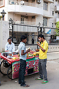 Residents buy fruit and tea from vendors outside their gated community, Gurgaon, India