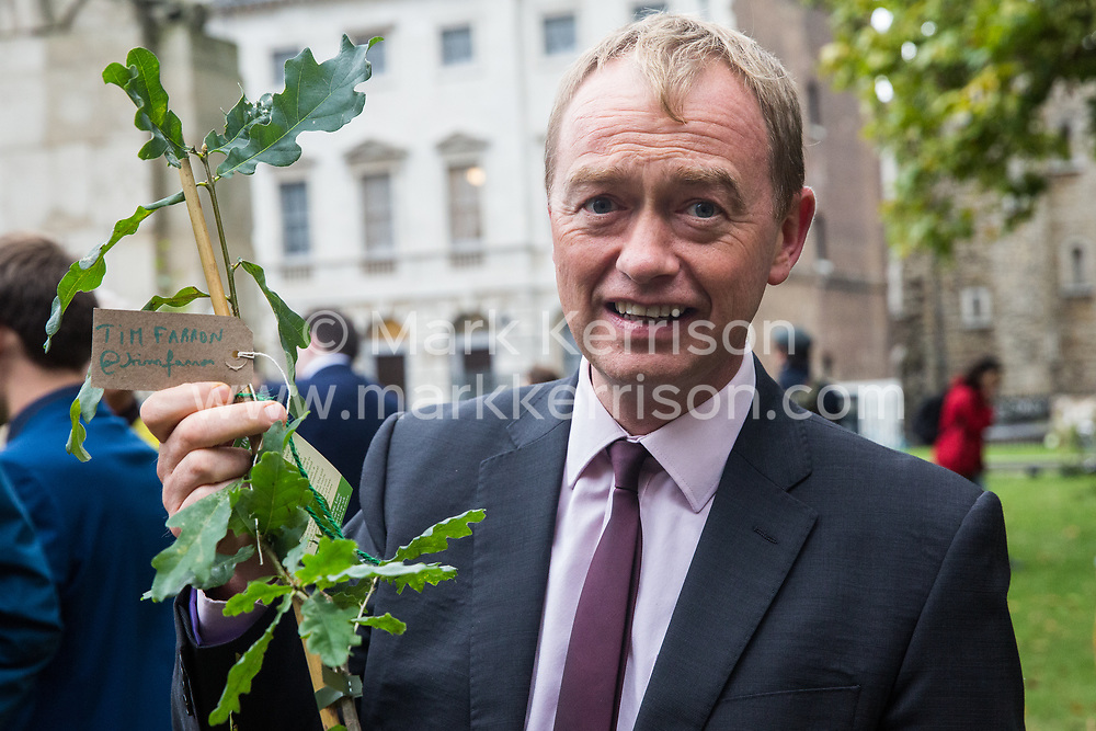 London, UK. 8 October, 2019. Tim Farron, Liberal Democrat MP for Westmorland and Lonsdale, receives a tree from Extinction Rebellion climate activists in Old Palace Yard on the second day of International Rebellion protests. Activists created a fledgling forest of potted native trees outside Parliament as part of an initiative named Reforest Earth and they were then presented to MPs to call on the government to plant billions of trees across the UK and support the planting of trillions more around the world.