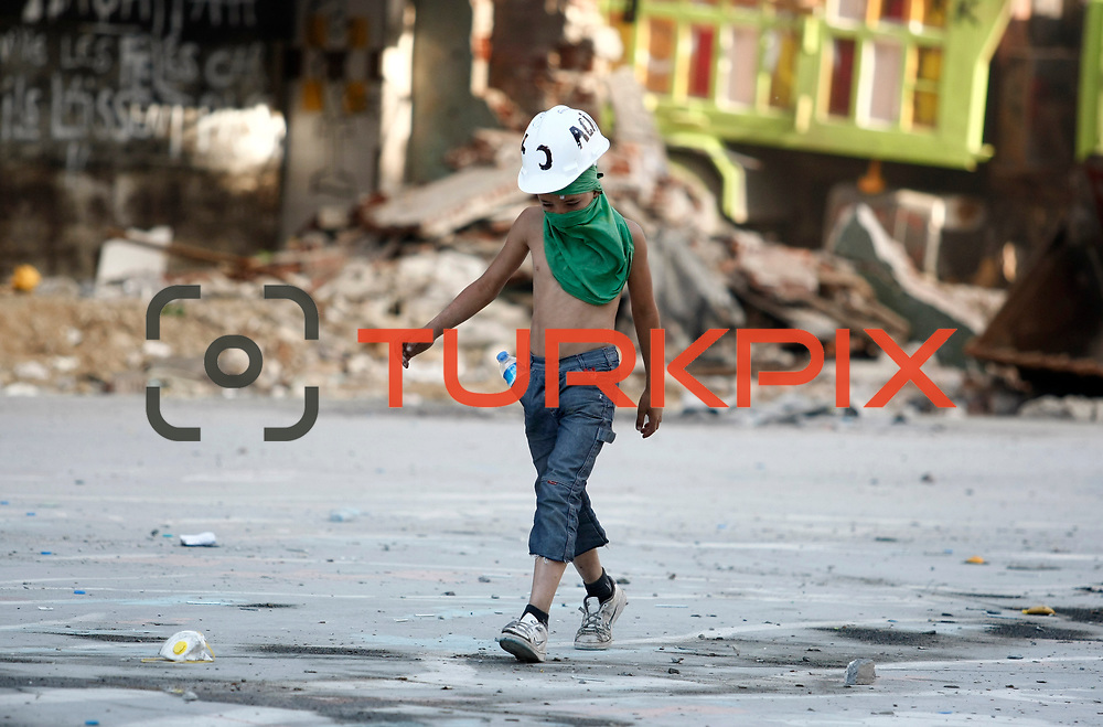 A young protestor walk seen during a clash with Turkish riot police at Taksim Square in Istanbul, Turkey, 11 June 2013. Photo by AYKUT AKICI/TURKPIX