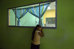 """Rosario, 14, peers into the neonatal ICU of Hospital San Benito. """"Our girls believe they were brought into this world to be a mother,"""" said Dr. Daniel Alvarez a pediatrician at the hospital. """"When she is 12 she is used to raising her siblings. She doesn't go to school, she is not literate. Some of these girls don't even learn Spanish, they only use their mother language. At a certain age, the only escape in their mind is to get involved with a boy, and do the same thing… be a mother, be part of the cycle. That's the cycle we are trying to break. We need to give more power to women to make good choices."""""""
