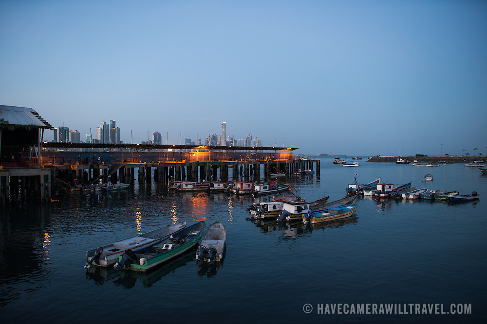 Small fishing boats anchored in a small protected harbor on the waterfront of Panama City, Panama, on Panama Bay.