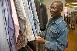 Man looking at clothes in a charity shop,