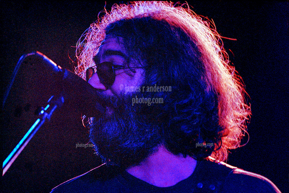 Jerry Garcia with The Grateful Dead Live at Huntington West Virginia 16 April 1978. A tight shot of Jerry looking right towards other band members and singing into the mic. Halo of light in his hair.