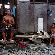 THE PHILIPPINES (Manila). 2009. Ramil Velasco, 48, with his game cock at his home in the Baseco area of Tondo, Manila. Photo Tim Clayton <br /> <br /> Cockfighting, or Sabong as it is know in the Philippines is big business, a multi billion dollar industry, overshadowing Basketball as the number one sport in the country. It is estimated over 5 million Roosters will fight in the smalltime pits and full-blown arenas in a calendar year. TV stations are devoted to the sport where fights can be seen every night of the week while The Philippine economy benefits by more than $1 billion a year from breeding farms employment, selling feed and drugs and of course betting on the fights...As one of the worlds oldest spectator sports dating back 6000 years in Persia (now Iran) and first mentioned in fourth century Greek Texts. It is still practiced in many countries today, particularly in south and Central America and parts of Asia. Cockfighting is now illegal in the USA after Louisiana becoming the final state to outlaw cockfighting in August this year. This has led to an influx of American breeders into the Philippines with these breeders supplying most of the best fighting cocks, with prices for quality blood lines selling from PHP 8000 pesos (US $160) to as high as PHP 120,000 Pesos (US $2400)..