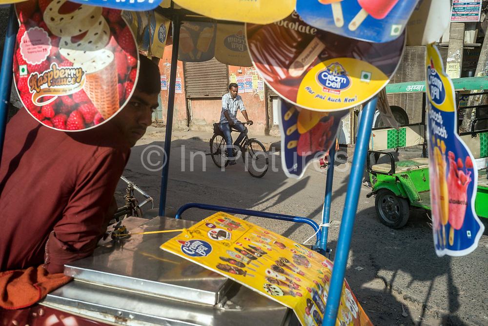 A man cycles past an ice-cream vendor near Nizamuddin East market, New Delhi, India