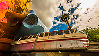 MoPop (Museum of Pop Culture) Building with the Seattle Center Monorail coming out of the building and the Space Needle on right; Seattle, Washington USA. The museum building was designed by Frank Gehry.