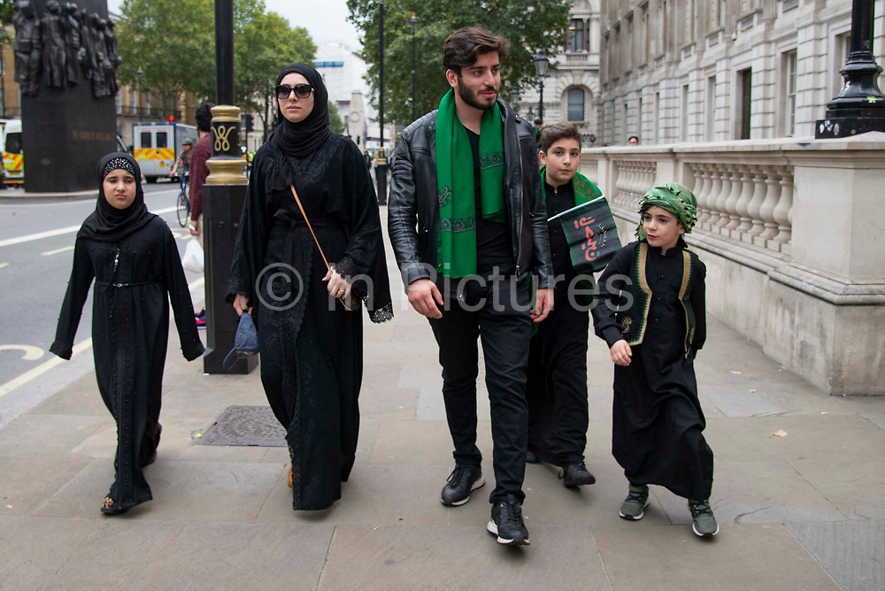 A young devote shia family with three children in traditional clothing at the commemoration of  the festival of Ashura in Whitehall, London, United Kingdom on 10th Spetember 2019. It marks the day that Husayn ibn Ali, the grandson of the Islamic prophet Muhammad, was martyred in the Battle of Karbala. Ashura is the tenth day of Muharram, the first month in the Islamic calendar.