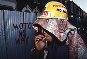 Protester smoking a cigarette at night with 'No Motorway' graffiti. Near to Road protestor squats indoors. Along the M11 route. Cambridge Park Wanstead, Leytonstone, London. <br /><br />The British Road Protesters movement began in the early 1990s when the Donga tribe squatted Twyford Down to save this beautiful site, a site of scientific interest SSI from the Ministry of transport's road building programme which threatened to destroy the landscape. The Dongas was the name of the ancient walkways, the paths trodden in the middle ages by people walking down to Winchester. A small tribe were joined by people of all walks of life who came to Twyford Down to defend it. A long hard battle over several years ended in the 'cutting' a new motorway built through this ancient monument and destroying it. <br /><br />The Road Protest movement in Britain continued for many years and more battles were fought in London against the MII both at Wanstead then in Leytonstone, and subsequently at Newbury, and in Sussex. the protesters were very inventive in their use of non violent peaceful direct action. They barricaded themselves into squats, made tree houses, tunnels and have huge demonstrations against the bailliffs, police and security who tried to force their way through the defences of this alternative environmental popular movement. Many of the roads were built eventually and many sites of great beauty lost, but the government had to stand down from its road building policy and eventually the programme was halted. the protests cost the government billions. Out of that movement grew many environmental NGOs who have to this day kept fighting for ecological and sustainable environmental solutions rather than following the cult of the car, petrol and roadbuilding..
