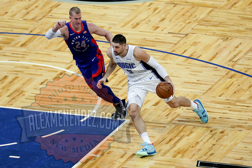 ORLANDO, FL - FEBRUARY 23:  Nikola Vucevic #9 of the Orlando Magic dribbles past Mason Plumlee #24 of the Detroit Pistons at Amway Center on February 23, 2021 in Orlando, Florida. NOTE TO USER: User expressly acknowledges and agrees that, by downloading and or using this photograph, User is consenting to the terms and conditions of the Getty Images License Agreement. (Photo by Alex Menendez/Getty Images)*** Local Caption *** Nikola Vucevic; Mason Plumlee
