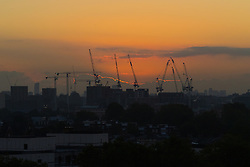 Primrose Hill, London, October 4th 2016. The sun lights up the edges of the clouds as dawn breaks across London, throwing the city's construction cranes into silhouette.