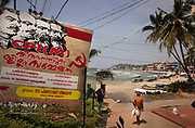 Poster for a communist conference overlooks Lighthouse Beach, a popular tourist destination on the Arabian Sea, on 28th February 2018 in Kovalam, Kerala, India.  Once a calm fishing village clustered around its crescent beaches and backed by a sea of cascading palms, Kovalam now competes with Varkala as Kerala's most developed resort. The touristed main stretch, Lighthouse Beach, is flanked by hotels and restaurants stretching back into the hillside from the shore. Today the largest political party in Kerala politics is the Communist Party of India Marxist.