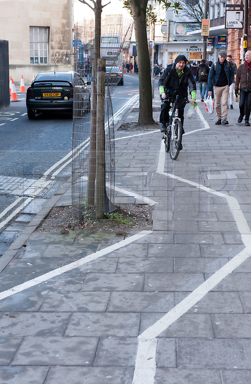 © Licensed to London News Pictures.  30/12/2014. Bristol, UK.  A contra-flow bike lane on the pavement zig-zags round trees in Nelson Street, central Bristol.  The one way road has been narrowed for adjacent major building work.  Photo credit : Simon Chapman/LNP